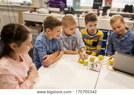 education, children, technology, science and people concept - group of happy kids with laptop computer playing and invention kit at robotics school lesson
