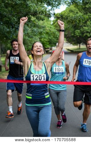 Happy woman crossing the finish line with raised arms