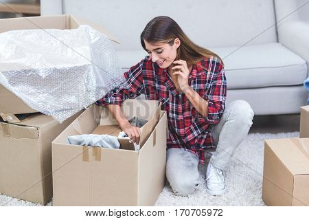 Beautiful woman unpacking carton boxes in his new house