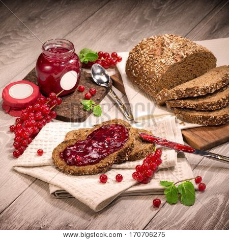 Jam currant bread composition on a wooden background