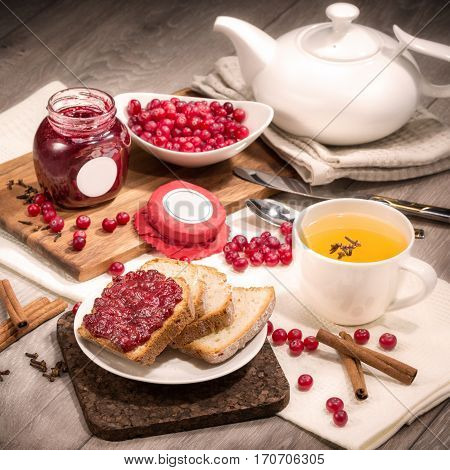 Lingonberry jam bread and tea composition on a wooden background