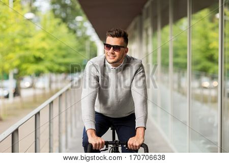 lifestyle, transport and people concept - happy smiling young man in sunglasses riding bicycle on city street