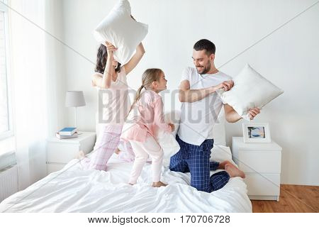 people, family and morning concept - happy child with parents having pillow fight in bed at home