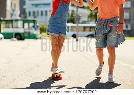 summer, extreme sport and people concept - happy teenage couple riding short modern cruiser skateboard on city street
