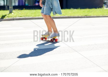 summer, extreme sport and people concept - teenage boy riding short modern cruiser skateboard on crosswalk in city