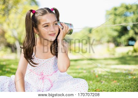 Cute young girl listening through tin can phone in park