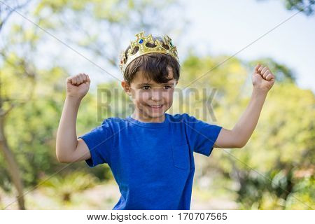 Boy wearing a crown and clenching his fists in excitement in park