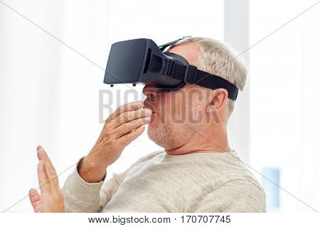 technology, augmented reality, gaming, entertainment and people concept - senior man with virtual headset or 3d glasses playing videogame at home