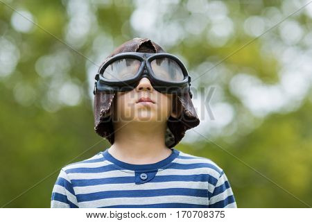Boy pretending to be an aviation pilot in park