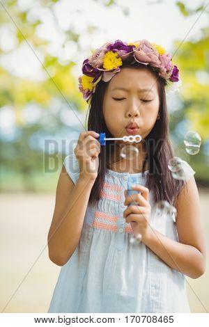 Girl wearing flower wreath blowing bubble wand in park