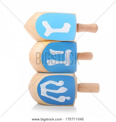 Wooden dreidels for Hanukkah on white background