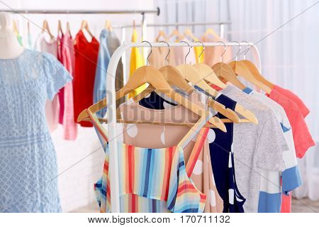 Fashionable clothes hanging on rack at room