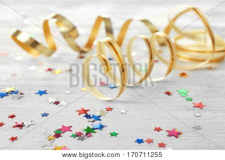 Colorful confetti and streamer on wooden background