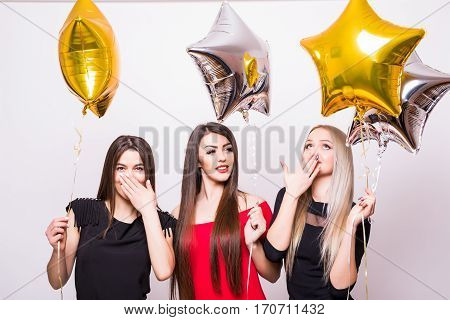 Three Lovely Young Women Have Fun And Holding Star Shaped Balloons Over White