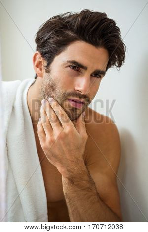 Close-up of young man looking checking his stubble in bathroom