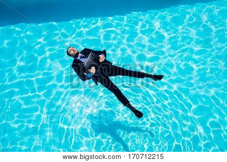 Dressed businessman in swimming pool on a sunny day