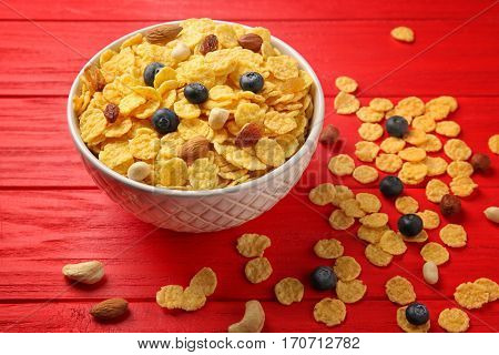 Bowl with cornflakes, nuts, raisins and blueberry on red wooden background