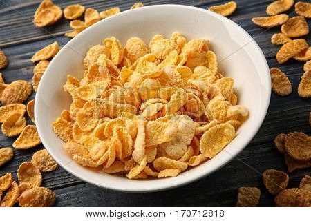 Bowl with cornflakes on grey wooden background, closeup