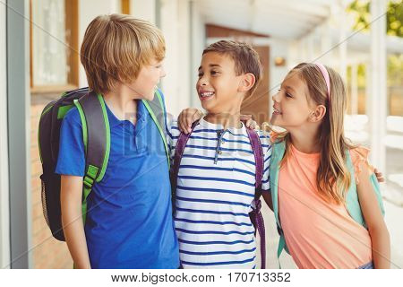 Smiling school kids standing in corridor and talking to each other at school