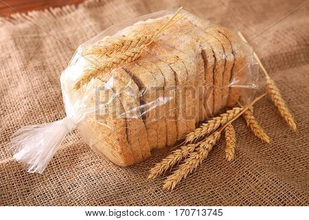 Sliced bread in plastic bag on sackcloth with wheat spikes closeup