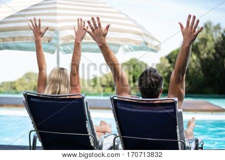 Rear view of couple near pool relaxing on sun lounger with hands raised