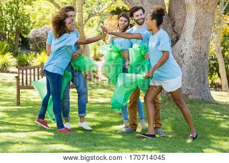 Group of volunteer having fun while collecting rubbish in park