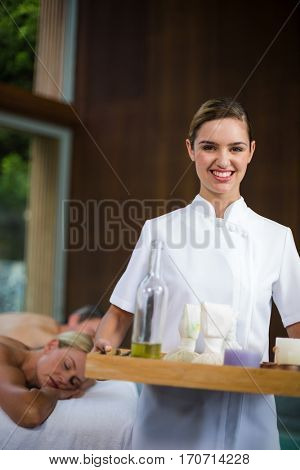 Portrait of female masseur holding a tray with spa therapy products