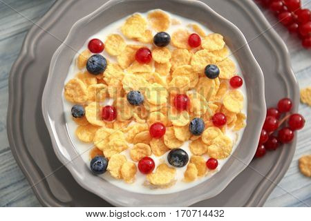 Tasty cornflakes with red currant and blueberries on gray wooden background