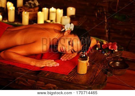 Massage of woman in spa salon. Girl on candles background in massage spa salon. Luxary interior in oriental therapy salon. Female have relax after sport.