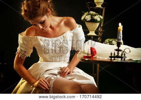 Wedding night preparing garter. Bride undressing and put veil on table. Candle illuminates house. Jewelry box next to girl. Baskets of flowers on black background.