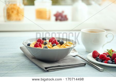 Tasty cornflakes with raspberries and blueberries on table