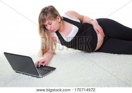 Young pregnant woman relaxing on carpet with laptop