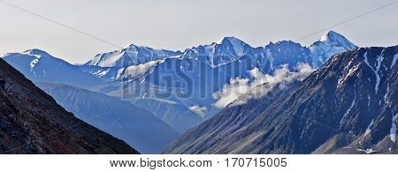 Alpine landscape. The top of the mountain are covered with glaciers flowing down to the rocky slope