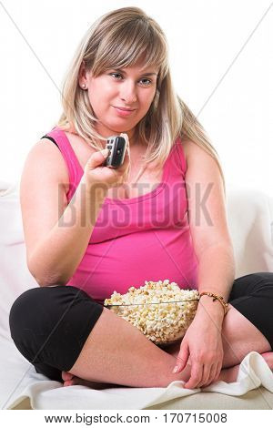 Beautiful fat young woman watching TV and eating popcorn