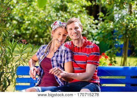 Couple in garden sitting on bench