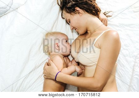 The woman is breastfeeding. Mum and daughter lie on the bed light.