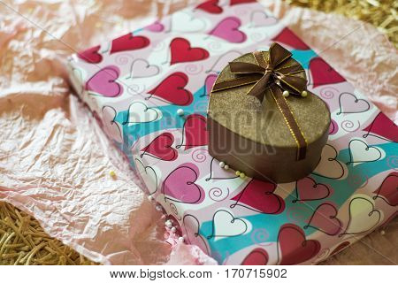 Heart-shaped gift box placed on another gift box wrapped with paper. Valentines gift set up.