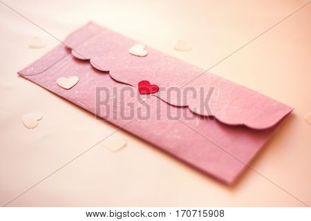 Pink color envelope sealed with red color heart shaped sticker. Valentines day object.