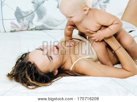 Mum and daughter lie on the bed. Woman and child having fun spending the weekend together. Family values.