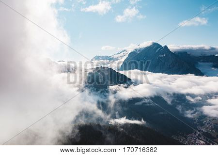 Creamy fog covered the glacier Marmolada in morning light. Great and gorgeous scene. Location place Val di Fassa valley, passo Sella, Dolomiti, Tyrol. Italy, Europe. Beauty world. Drone photography.