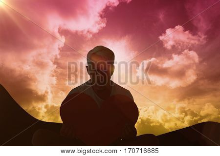 Upset man sitting holding heart shape against sky and mountains