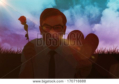 Geeky hipster holding a red rose and heart card against sky and field