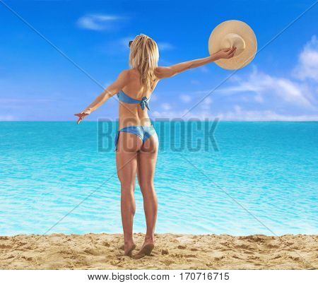 Feeling the sun at beautiful beach. sunbathing fitness woman looking the sea waiting the boat.