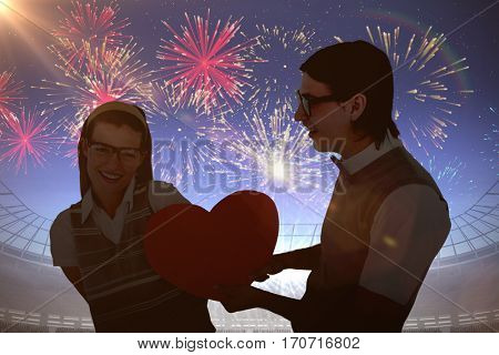 Geeky hipster offering red heart to his girlfriend against fireworks exploding over football stadium