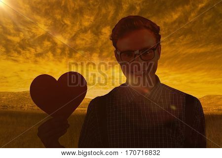 Geeky hipster holding a heart card against beautiful african scene