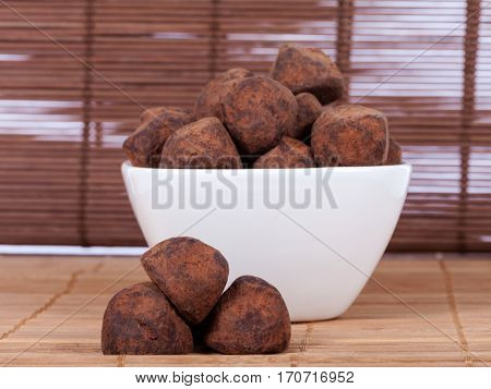 Black chocolate truffles in a white bowl covered with cinnamon powder