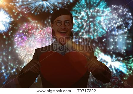 Geeky businessman smiling and holding heart card against colourful fireworks exploding on black background