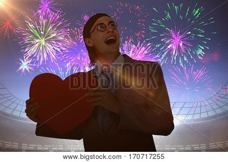 Geeky businessman smiling and holding heart card against fireworks exploding over football stadium
