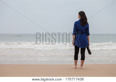 Lonely and depressed woman standing in front of the sea in a deserted beach on an Autumn day.
