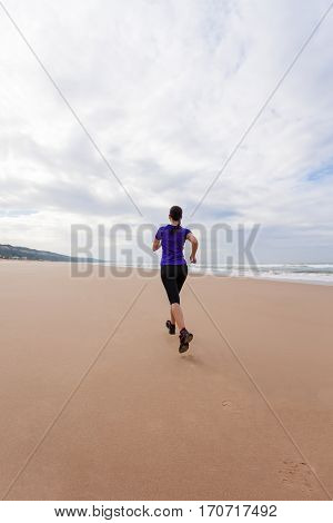 Female athlete running at the beach on an Autumn day.